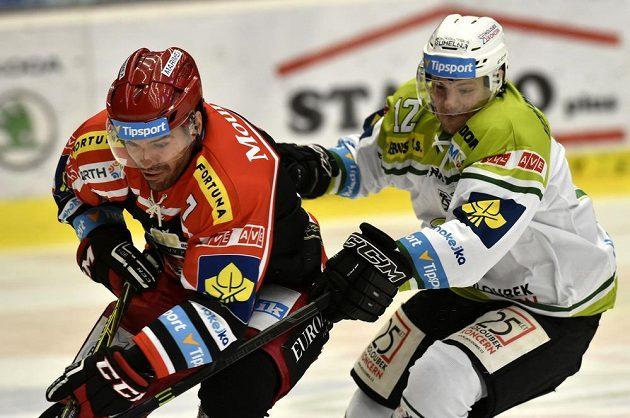 Zleva Peter Frühauf z Hradce a karlovarský David Gríger v souboji o puk.