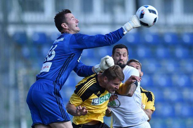 Brankář Jan Laštůvka (vlevo) z Karviné vyráží míč před Magerou z Mladé Boleslavi.