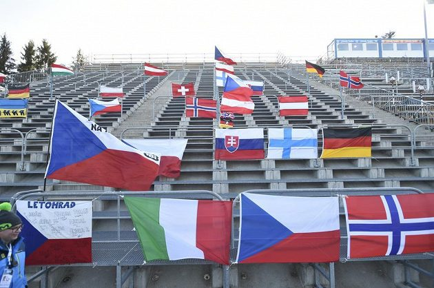 Lidé z organizačního výboru rozvěsili před sprintem vlajky na prázdné tribuně biatlonového areálu v Novém Městě na Moravě.