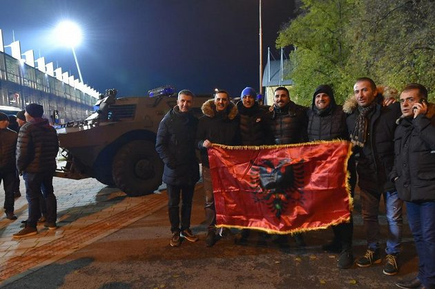 Fanoušci Kosova s albánskou vlajkou před policejním transportérem.
