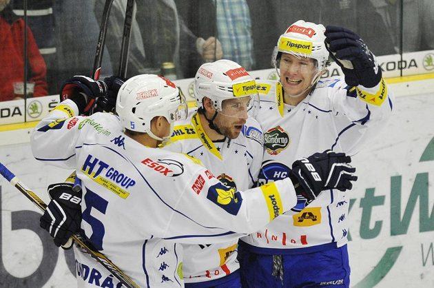 Hokejisté Komety Brno zleva Tomáš Vondráček, Jakub Koreis a Vilém Burian se radují z druhého gólu na ledě Boleslavi.
