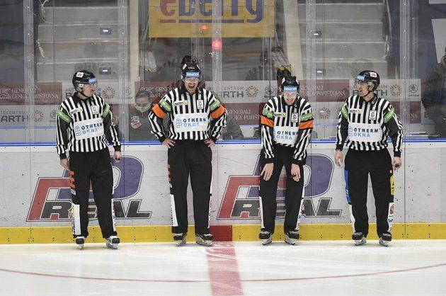 Hokejoví rozhodčí se usmívají před začátkem utkání.