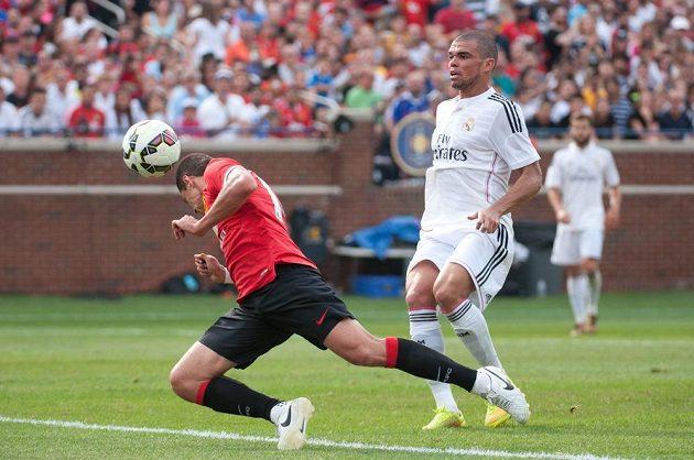 Útočník Manchesteru United Javier Hernández právě skóruje hlavou proti Realu Madrid, marně jej stínuje stoper Bílého baletu Pepé.