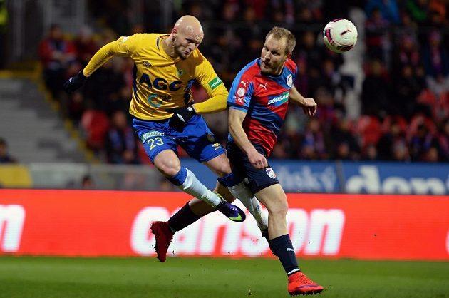 Obránce Teplic Zurab Tsiskaridze (vlevo) odvrací míč před plzeňským kapitánem Danielem Kolářem.