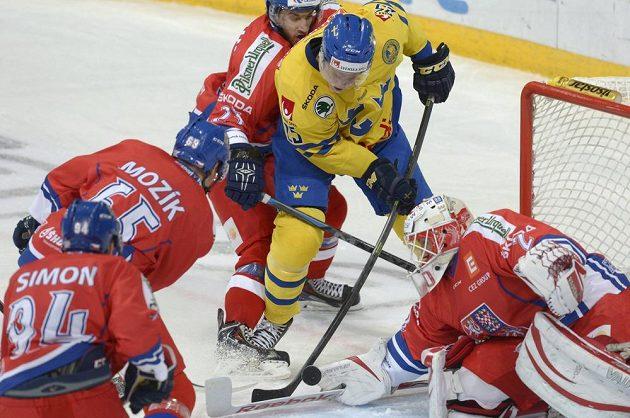 Švédský útočník Andreas Engqvist (ve žlutém dresu) se snaží zasunout puk za českého brankáře Šimona Hrubce.