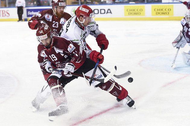 Útočník Mountfieldu Jiří Šimánek v souboji s dvojicí hokejistů Rigy.