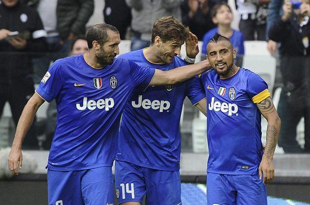 Fotbalisté Juventusu Giorgio Chiellini (vlevo) a Fernando Llorente gratulují Arturo Vidalovi (vpravo) k brance v utkání proti Palermu.