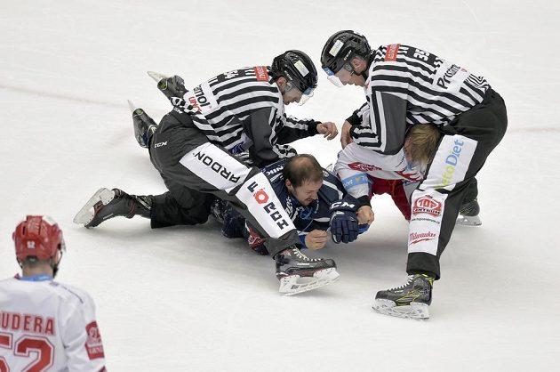 Rozhodčí řeší souboj Jiřího Polanského z Třince (vpravo) a Petra Straky z Plzně v semifinále hokejové extraligy.