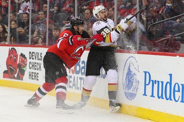 Obránce New Jersey Devils Andy Greene (6) přišpendlil českého útočníka Vegas Golden Knights Tomáše Hyku na mantinel během utkání NHL.