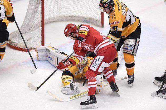 Jiří Polanský z Třince (v červeném) se snaží dorazit puk za záda litvínovského gólmana Pavla Francouze.