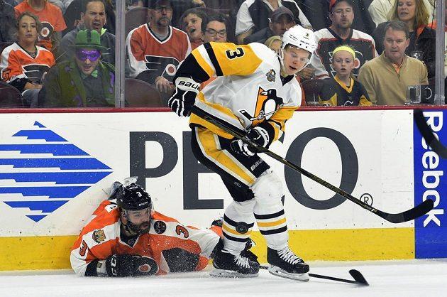 Český zadák Radko Gudas (3) z Philadelphie se snaží i vleže sebrat puk obránci Pittsburghu Olli Määttämu (3).