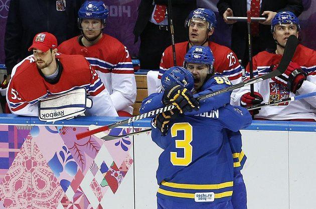 Erik Karlsson (č 65) oslavuje gól se spoluhráčem Oliverem Ekmanem-Larssonem před smutnou českou střídačkou.