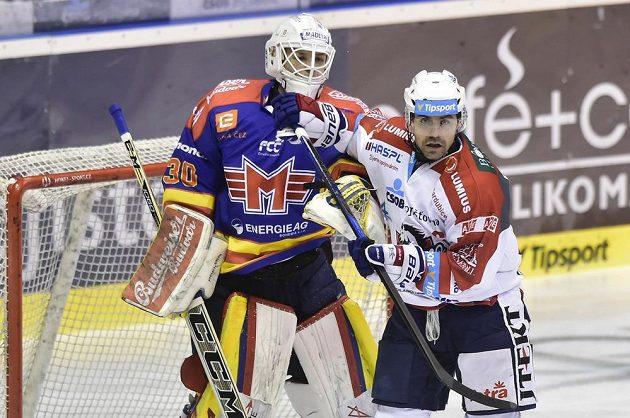 Brankář Motoru Petr Kváča, kterému se snaží bránit ve výhledu Tomáš Rolinek z Pardubic během utkání 1. kola baráže o hokejovou extraligu.