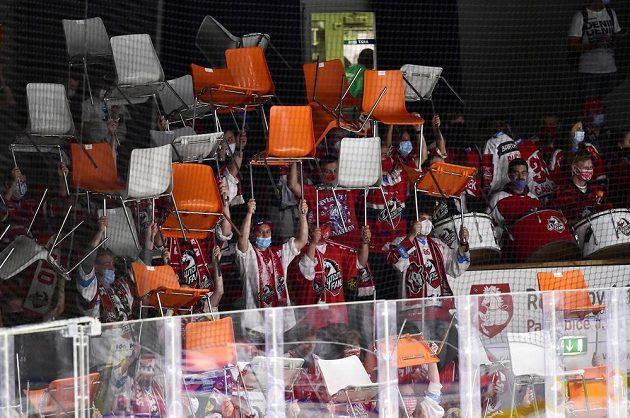 Fanoušci Pardubic drží nad hlavami židle, které jim klub v rámci protikoronavirových opatření připravil do sektoru na stání.