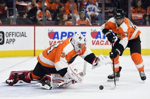 Gólman Philadelphie Flyers Petr Mrázek chytá puk v utkání NHL proti Columbusu. Situaci přihlíží jeho spoluhráč Shayne Gostisbehere.