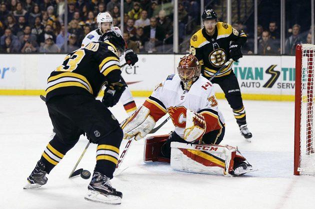 Hvězda Bostonu Brad Marchand (63) zkouší překonat českého brankáře Calgary Flames Davida Ritticha v utkání NHL.