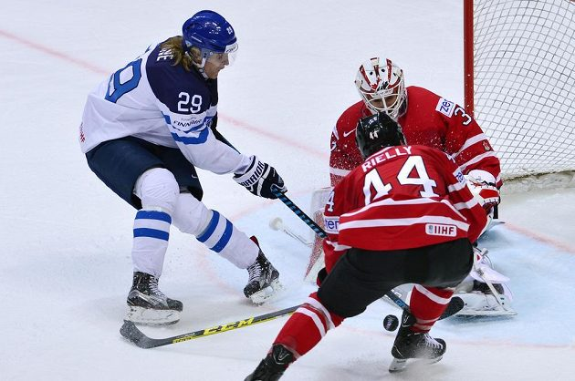 Fin Patrik Laine se snaží protlačit puk za záda kanadského gólmana Cama Talbota.