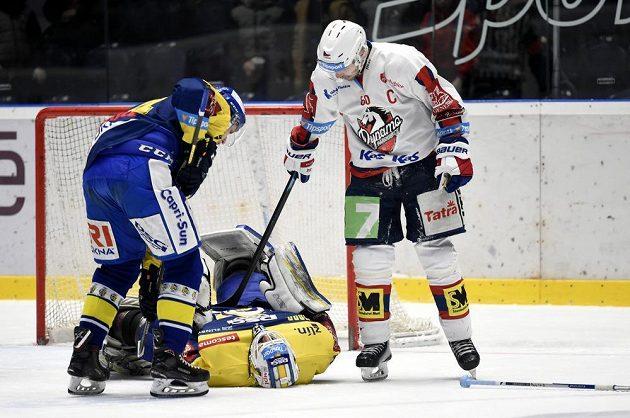 Brankář Zlína Libor Kašík je na lopatkách, pardubický Tomáš Rolinek do něj lehce šťouchá hokejkou. Vše sleduje jeden ze zlínských obránců.