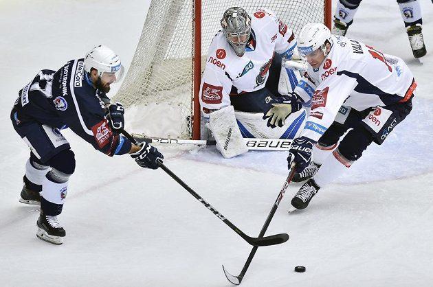 Plzeňský hokejista Milan Gulaš rozehrává před brankou Chomutova, v níž je Justin Peters. Bránit se snaží chomutovský Juraj Valach.