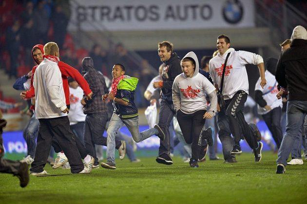 Fanoušci Slavie utíkají z hrací plochy před policejními těžkooděnci.