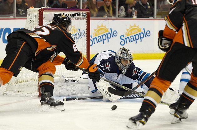Brankář Winnipegu Ondřej Pavelec blokuje střelu Rickard Rakella z Anaheimu.