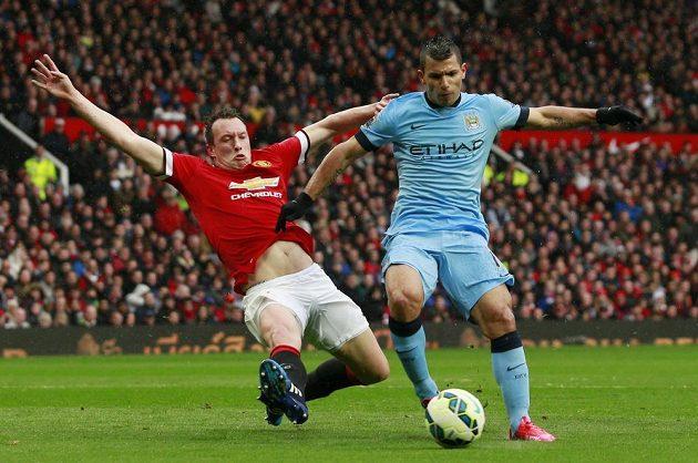 Phil Jones z Manchesteru United se skluzem snaží odebrat míč útočníkovi Manchesteru City Sergio Agüerovi.