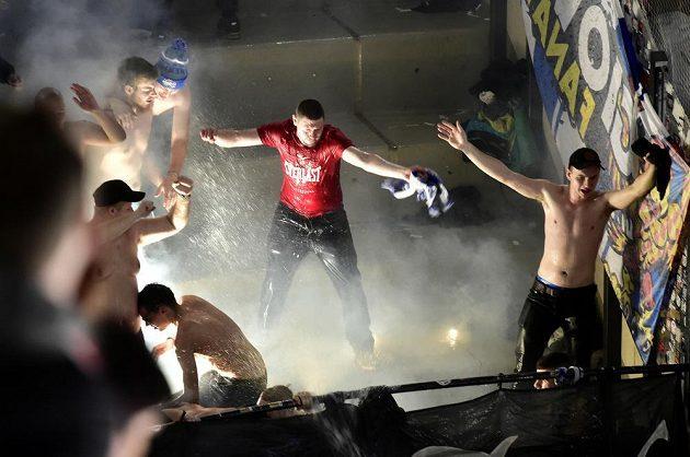 Hasiči stříkají vodu do sektoru hokejových fanoušků Komety Brno, kteří v závěru zápasu v Pardubicích použili pyrotechniku.