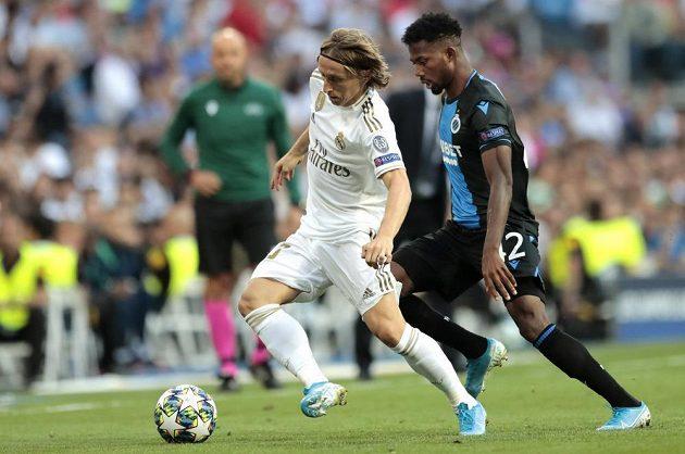 Fotbalista Luka Modrič si kryje míč před Emmanuelem Dennisem z FC Bruggy v utkání Ligy mistrů.