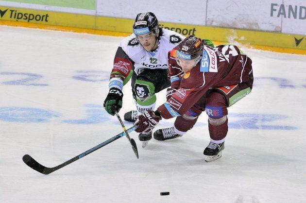 Mladoboleslavský hokejista František Hrdinka se natahuje za pukem spolu se sparťanem Tomášem Pšeničkou v extraligovém utkání.