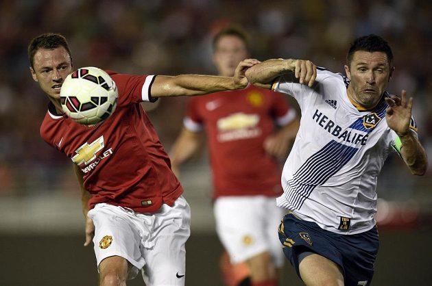 Obránce Manchesteru United Jonny Evans (vlevo) v souboji s útočníkem Los Angeles Galaxy Keanem.