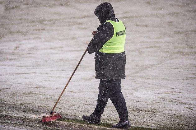 Pořadatel uklízí sníh na zasněžené Julisce před utkáním 19. kola Synot ligy mezi Duklou a Spartou, které nakonec bylo odloženo.