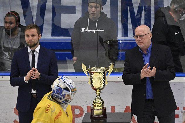 Jihlavský brankář Maxim Žukov po prohraném utkání smutně projíždí kolem poháru pro vítěze první ligy. Vpravo je šéf soutěžePavel Setikovský.