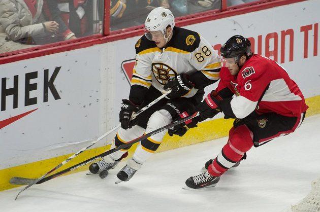 Český útočník David Pastrňák (88) z Bostonu je bráněn Bobbym Ryanem (6) z Ottawy v zápase NHL.
