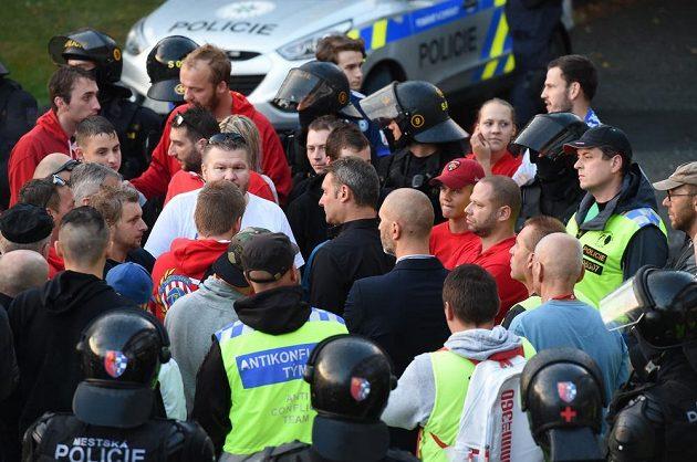 Trenér Brna Svatopluk Habanec (uprostřed v černé košili) hovoří před stadionem s fanoušky Brna mezi policejním kordonem a členy antikonfliktního týmu po prohraném utkání v Olomouci.
