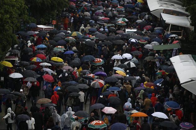 Hromadný úprk fanoušků před dešťovými přeháňkami.