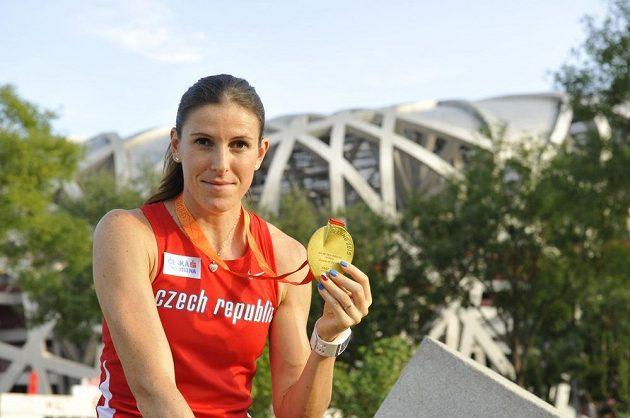 Zuzana Hejnová pózuje před olympijským stadiónem Ptačí hnízdo se zlatou medailí.