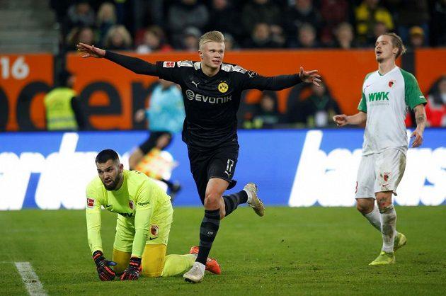 Český brankář Augsburgu Tomáš Koubek je na kolenou. Norský útočník Erling Haaland naopak slaví. V soutěžní premiéře za Dortmund třikrát skóroval.