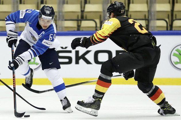 Finský šikula Mikael Granlund (vlevo) kouzlí s pukem, zastavit se ho snaží Sebastian Uvíra z Německa.