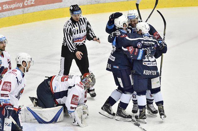 Hokejisté Plzně se radují z gólu, na kolenou je brankář Chomutova Justin Peters.