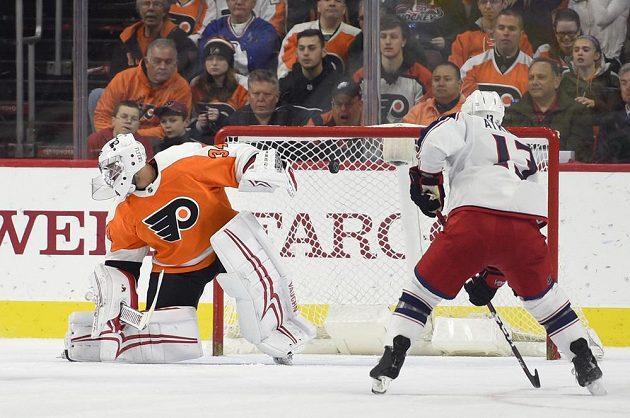 Gólman Philadelphia Flyers Petr Mrázek, před jeho branku najíždí Arťjom Panarin z Columbusu.