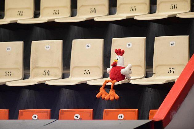 Plyšový maskot HC Olomouc sedí na prázdné tribuně.