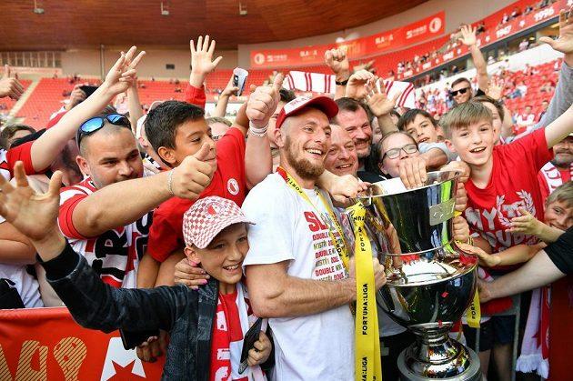Slávista Vladimír Coufal spolu s fanoušky pózuje s mistrovským pohárem.