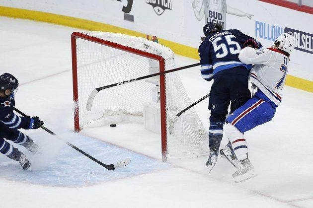 Útočník Montrealu Canadiens Jake Evans (71) sice poslal touš do sítě, gól ale nestihl oslavit, protože jej zasáhl nevybíravým zákrokem Mark Scheifele (55) z Winnipegu Jets.