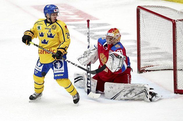 Švédský hokejista Andreas Wingerli v akci před ruským brankářem Alexandrem Samonovem během utkání na Švédských hokejových hrách.