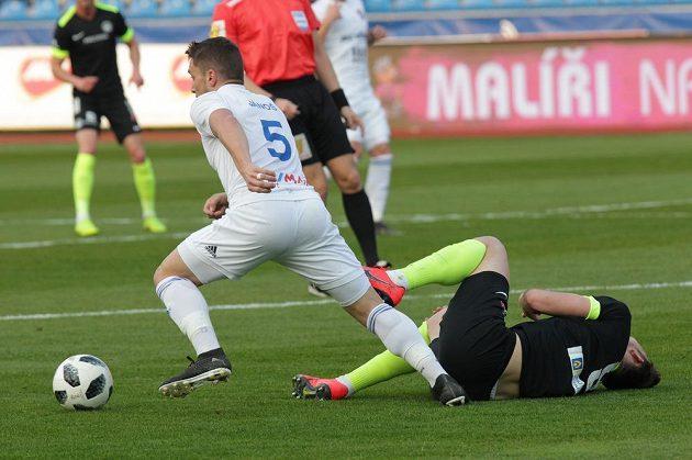 Adam Jánoš z Ostravy vyjíždí s míčem, na zemi po souboji útočník Liberce Libor Kozák.
