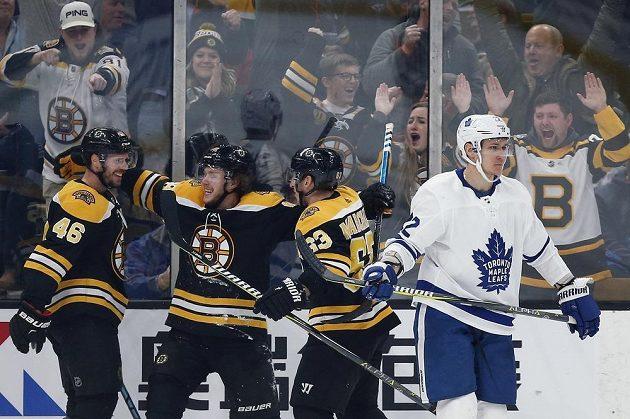 David Krejčí (vlevo), David Pastrňák a Brad Marchand (vpravo) oslavují branku, vstřelenou do sítě Toronta v zápase NHL.