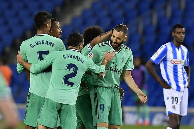 Kanonýr Realu Madrid Karim Benzema slaví se spoluhráči vstřelený gól v utkání se San Sebastianem. Soupeř se zlobil, že při gólové akci údajně zahrál rukou a branka neměla platit.