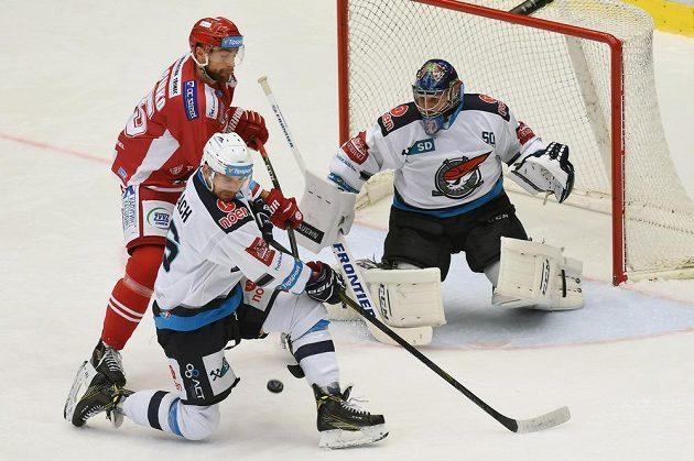 Třinecký útočník Tomáš Marcinko (vlevo) a obránce Chomutova Juraj Valach bojují před brankářem Pirátů Jánem Lacem.