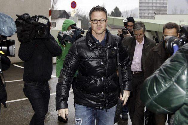 Michaelův bratr Ralf Schumacher míří do nemocnice skrz shluk novinářů.