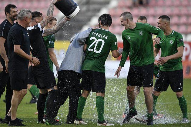 Fotbalisté Příbrami se radují, po zápase, kdy udrželi nejvyšší soutěž, kropí vodou trenéra Romana Nádvorníka.